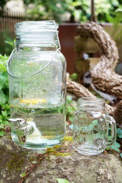 Getränkespender aus Glas mit Zapfhahn als Durstlöscher im Sommer im Garten