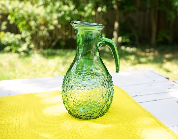 Grüner Glaskrug mit Noppenmuster für den sommerlich gedeckten Tisch im Boho Look