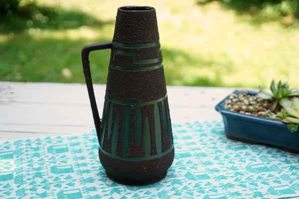 Eine schöne, schwarze Vintage Vase aus den 60er Jahren mit FAT LAVA Glasur und grafischem Design in dunklem grün für das Zuhause im angesagten Ethno Look.